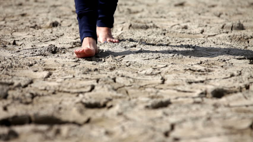 Barefoot person walking on the cracked soil towards the camera