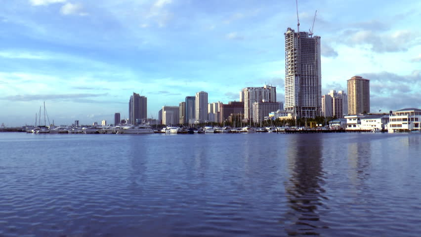 time lapse footage, video of Manila bay skyline with docked boats and yachts and buildings at the background.