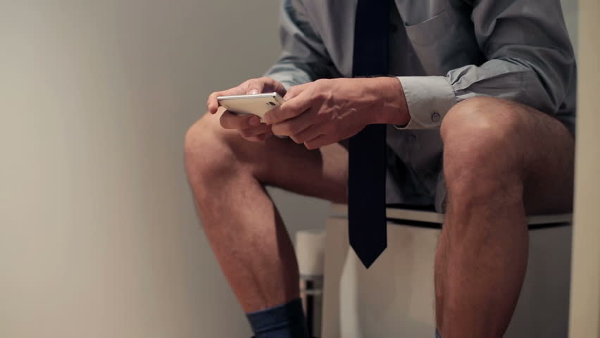 Businessman with smartphone sitting on toilet