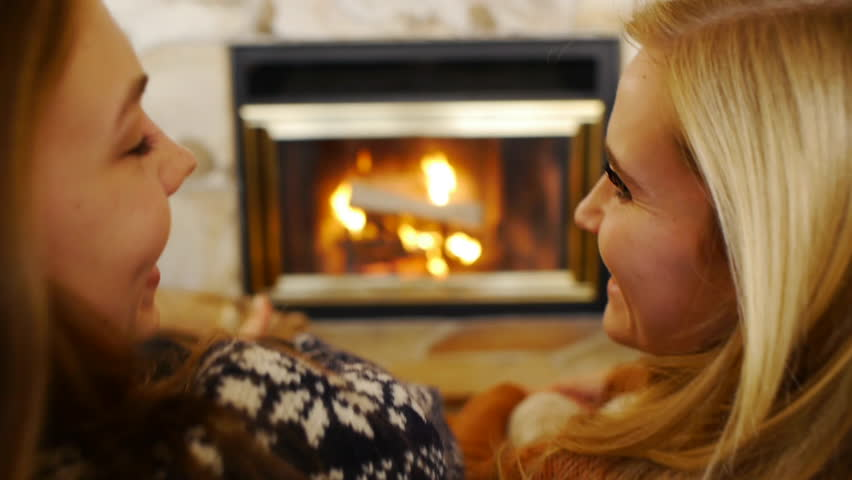 Over-Shoulder Shot Of Teen Girls Chatting In Front Of A Fireplace - HD stock footage clip