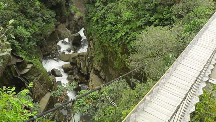 Suspended bridge over Pastaza river and Pailon del Diablo waterfall in Ecuadorian Andes, popular touristic destination in Ecuador - HD stock footage clip