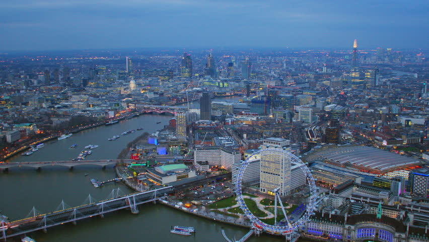 4K Aerial shot of Central London at dusk or night with a view of the River Thames, trains pulling into Waterloo Station, St Paul's Cathedral & The Shard