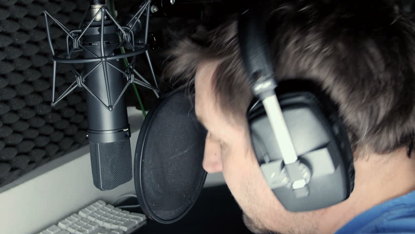 Male singer recording in a sound proof vocal booth with large condenser microphone and fully enclosed headphones.