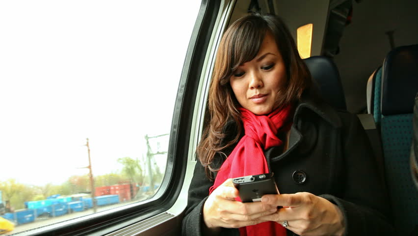 Young Asian Woman Texting with Cell phone While Traveling by Train