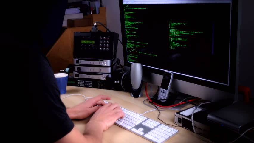 A computer programmer or hacker busy at work surrounded by streaming code on screen, ISDN and broadband connections and disk drives and wires wearing a balaclava to disguise face.