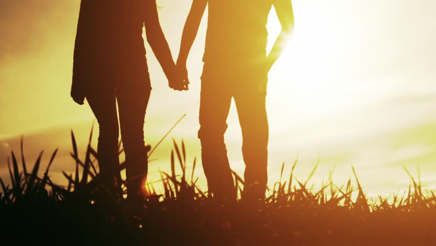 Young Couple Man Woman Walking Toward Sunset Silhouettes