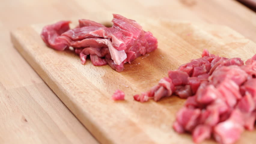 HD 1080 static: Chef cuts steak onto fine slices and cubic shapes; closeup,