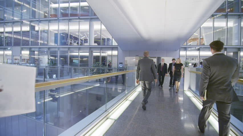 Attractive diverse business group walking through one floor of a large contemporary office building. In slow motion.