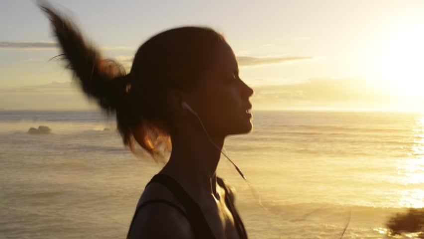 Mixed race woman runner running on beach road