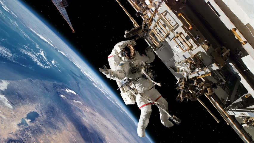 Astronaut outside the International Space Station on a spacewalk with a dramatic view of the Earth rotating in the background.