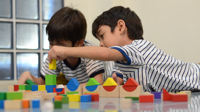 Little  asian mix arabic sibling boy playing block together - HD stock video clip
