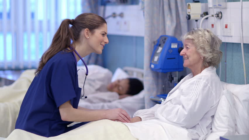 Caring nurse chats with an elderly female patient on a hospital ward. - HD stock footage clip