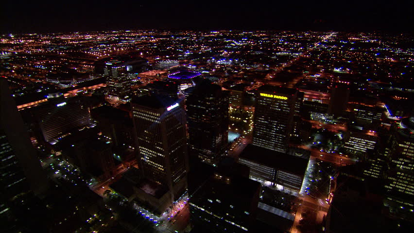 Overview Phoenix Arizona. Far view of the US Airways Center in Phoenix, Arizona. Features bright purple lights, lens flares, beautiful cityscape scenery and a view of the Wells Fargo building.
