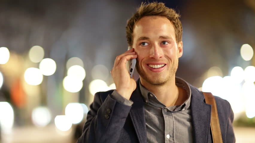 Smart phone man calling on mobile phone at night in city. Handsome young business man talking on smartphone smiling happy wearing suit jacket outdoors. Urban male professional in his 20s.