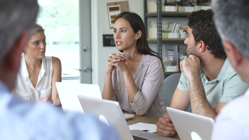 Group of architects sitting around table having meeting and using laptops as focus is pulled from over the shoulder in the foreground to female speaker.