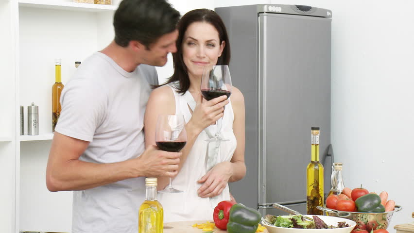 Happy couple drinking wine and eating salad in the kitchen at home. Footage in high definition - HD stock footage clip