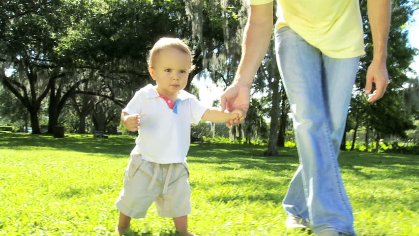 Happy young male Caucasian child holding protective fathers hand practicing walking grass outdoors park - Loving Father Caucasian Boy Toddler Barefoot Outdoors Grass