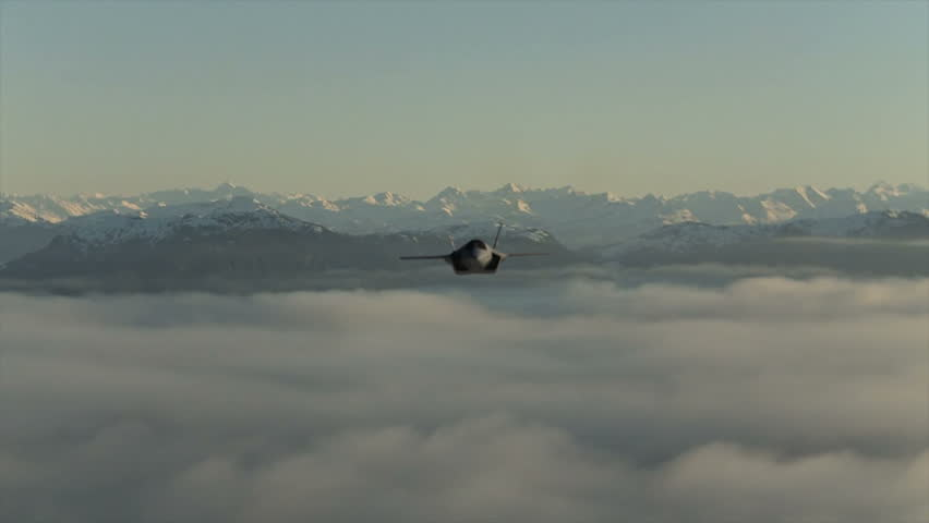 A F-35B Lightning II Joint Strike Fighter flying above the clouds rolls and descends.  High production value 3D animation (CGI).