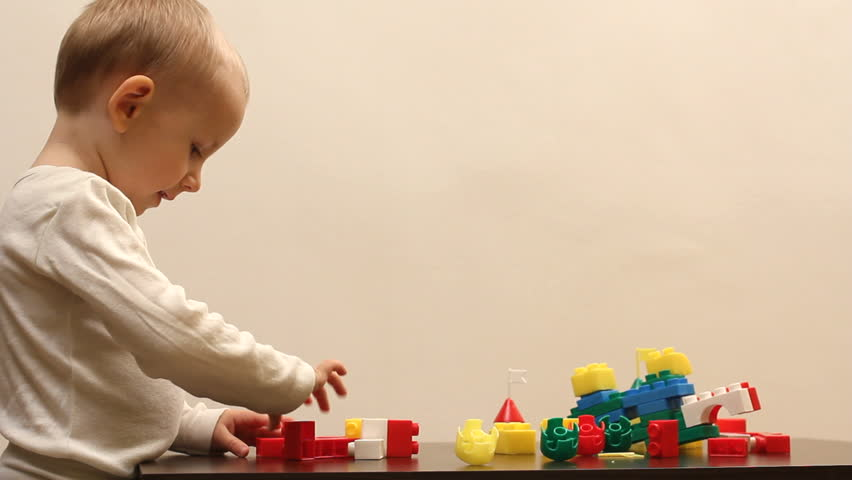 Sweet little boy play with colored lego pieces