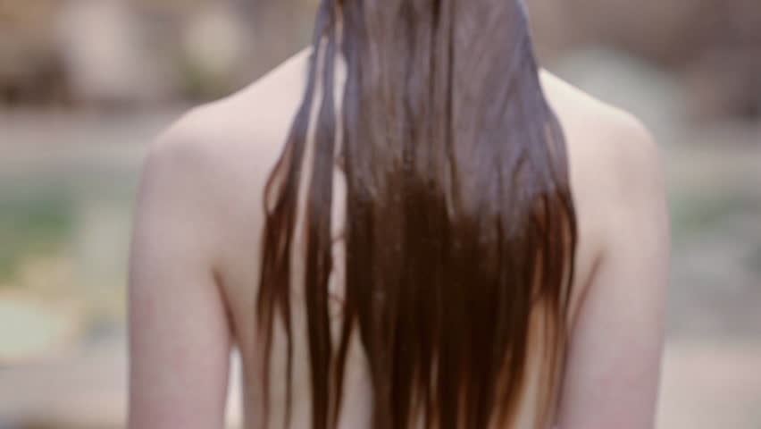 Rear view of a nude woman coming out of a pool