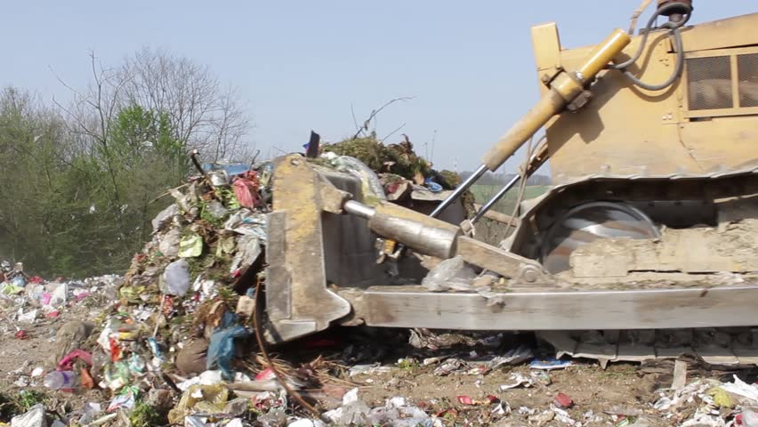 8/35 SRBIJA,KRUSEVAC,2014. Bulldozer (tractor) pushes a pile of trash at landfill. Vehicle flattening garbage to waste.Bulldozer moves non biodegradable garbage at the dump.Truck working on dump.30fps - HD stock footage clip