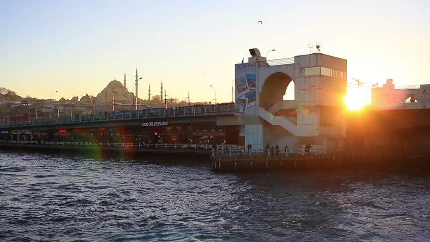 Bosphorus sightseeing tour boat leaving from Galata Bridge on sunset. Galata Bridge a 490 m long bascule bridge spans the Golden Horn and connects Galata Coast to Old City of Istanbul.