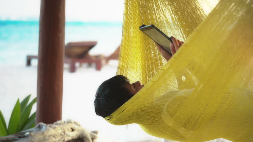 latin woman reading ebook using a electronic tablet in hammock at Mexican Caribbean