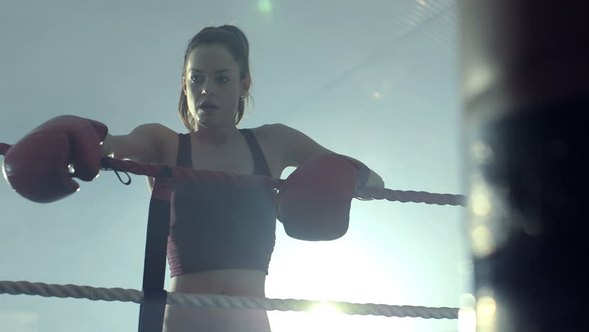 Female Boxer rests on the topes of the Ring, then turns to back to her fight.