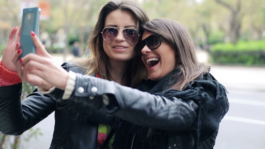 Two happy girlfriends taking photo with their smartphone in the city
