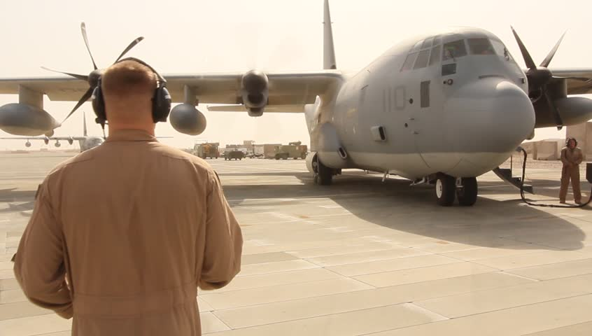 Afghanistan, Circa 2011: US Air Force Airmen readies Hercules c-130 aircraft for engine start-up on tarmac of airfield in Afghanistan, Circa 2011