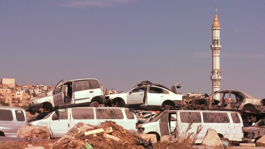 PALESTINIAN TERRITORIES, ISRAEL CIRCA 2013 - A junkyard stands in front of mosque in the Palestinian Territories and Judean Hills of Israel.