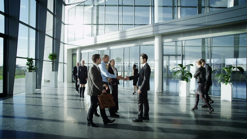 Business people meet and shake hands in large modern office building