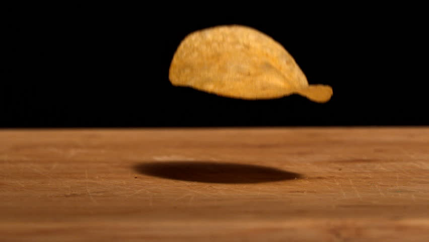 Chip falling on wooden table in slow motion