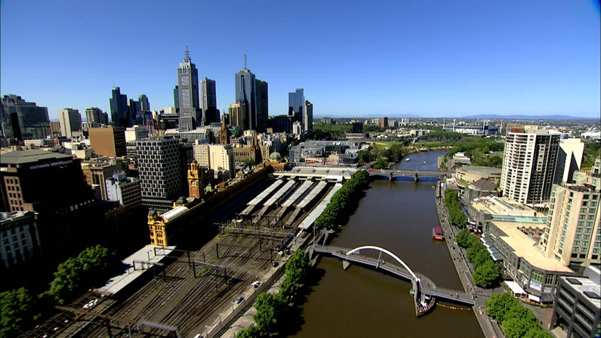 An aerial shot of Melbourne City, along the Yarra River past Flinders Railway Station and federation Square towards the MCG, Melbourne Cricket Ground