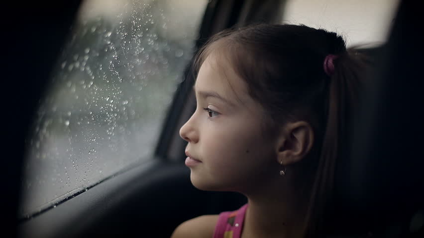 little girl in the car in raining child looking out the window car rides.