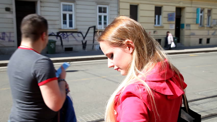 Blond girl in red coat standing on the street