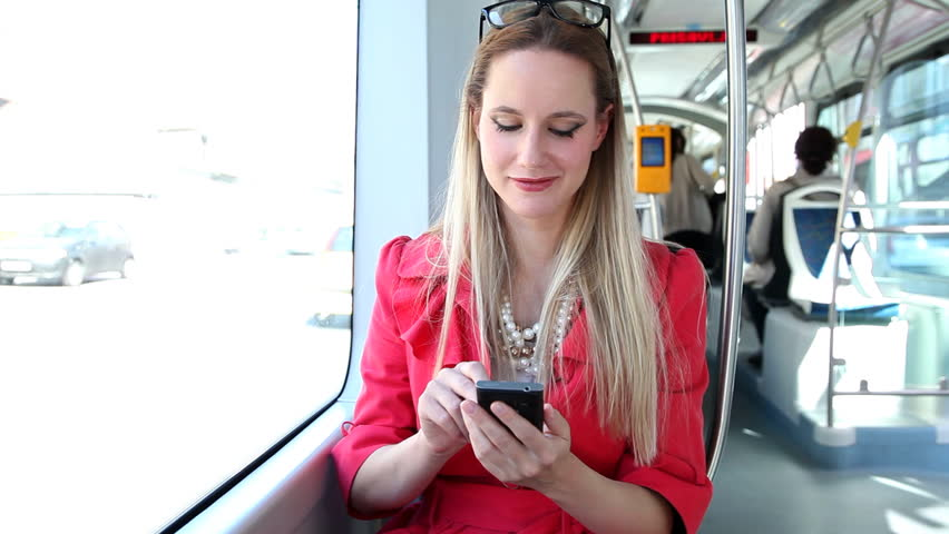 Young blond woman riding tram, typing on mobile phone, smiling