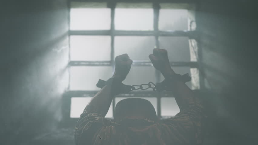 Prisoner with chained hands pray to the Lord. Dove of hope flying through window.