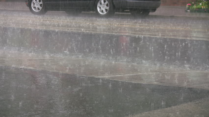 Heavy rain on the street. Summer thunderstorm with hard rain falling on a city street.