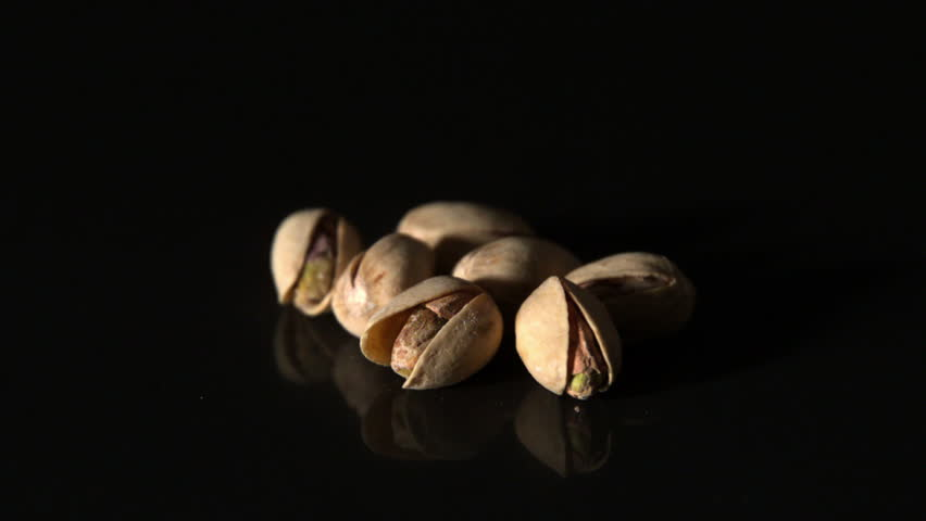Pistachio nuts falling on black surface in slow motion