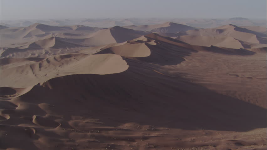 Shadowed Desert Sand Dunes. A beautiful aerial view of rolling sand dunes in a desert landscape. Stunning shadows are cast across the dunes as the sun begins to set.