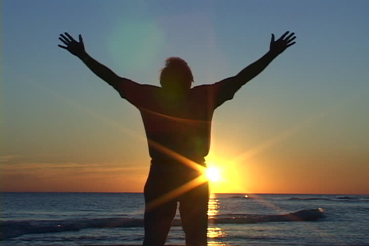 Mature man with hands raised, rejoices in prayer and worship at sunset on the beach. Shot on miniDV from a tripod. - SD stock video clip
