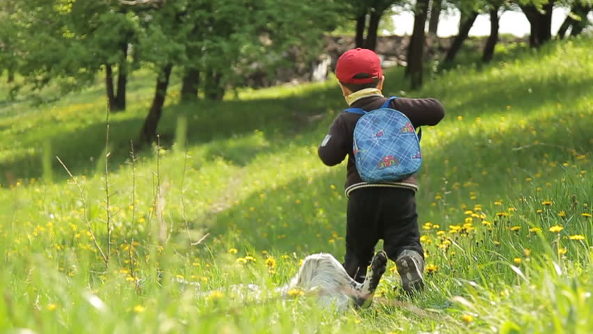 A boy in a red cap with a knapsack on a footpath runs through the green meadow. Face is not visible