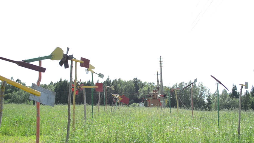 Hand made pinwheel collection spin in wind. Windmills made of old car and wood parts in garden high grass. - HD stock footage clip