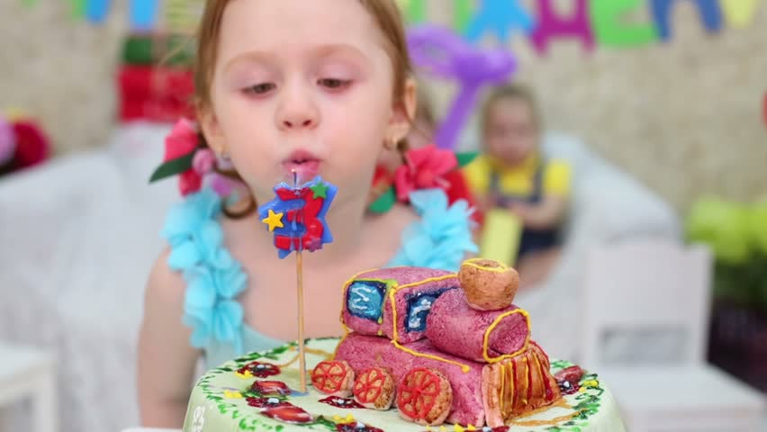 Little cute girl blows out candle on cake and other kids look at she at children party. Focus on girl, cake