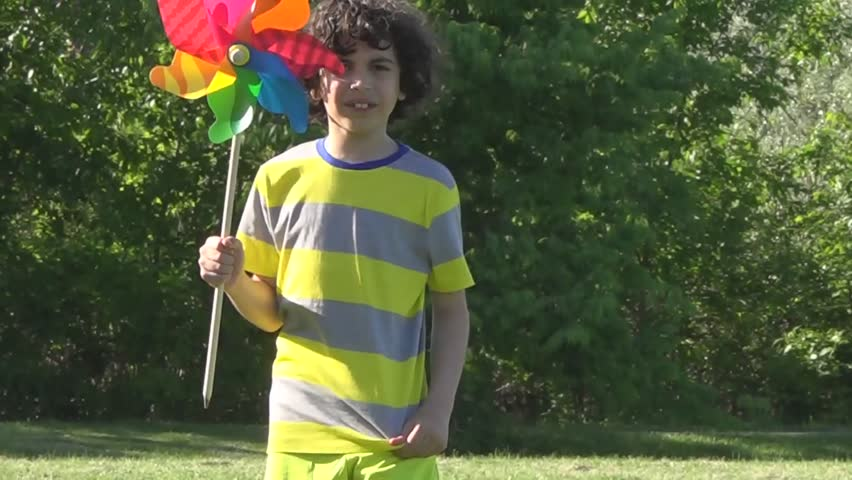 Hispanic child having fun outdoors with a reguilete. Using a rehilete to spend quality time during Summer. Boy enjoying Spring using pinwheels. Inexpensive time. Free things in life.