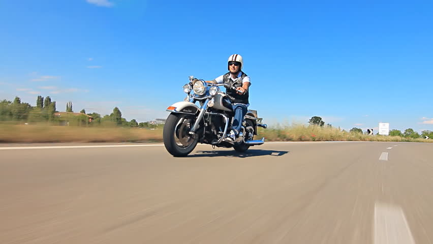 man riding his motorcycle  on a highway follow shot car point of view