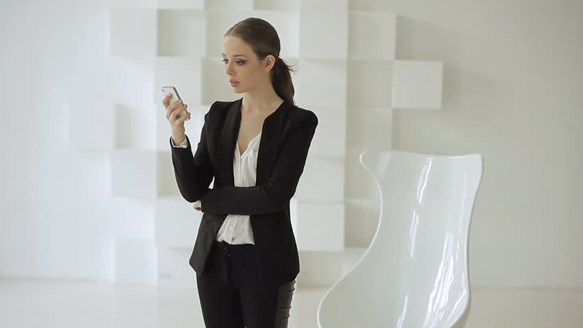 Beautiful young woman standing in trendy office and using her smartphone (texting, speaking).
