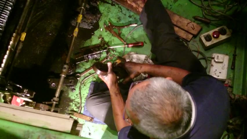 Escalator maintenance - Old mechanic man attaching a new roller for an escalator - 4K stock footage clip