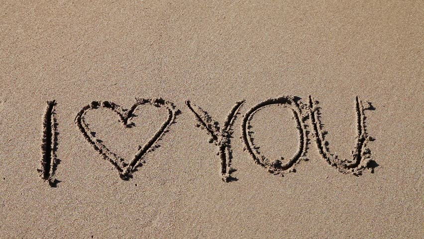 I Love you written in the sand being washed away  - HD stock footage clip